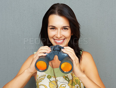 Buy stock photo Smiling young woman holding binoculars against the wall