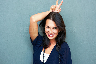 Buy stock photo Smiling woman with hand on head with victory sign