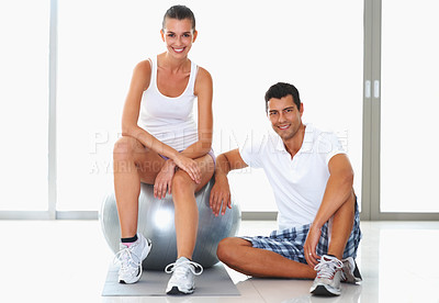 Buy stock photo Young woman sitting on exercise ball with trainer sitting beside her