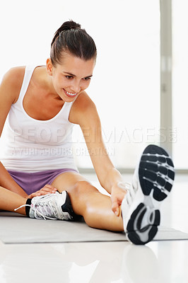 Buy stock photo Smiling young woman doing stretching at gym