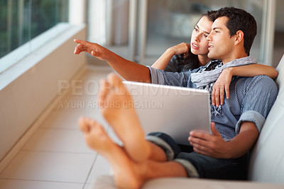 Buy stock photo Young man showing something to his girlfriend while working on laptop