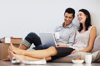 Buy stock photo Beautiful young couple working on laptop at home
