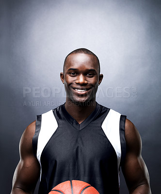 Buy stock photo Portrait of a happy afroamerican guy holding a basketball against black background