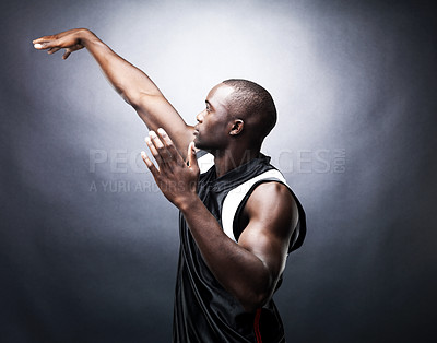 Buy stock photo Portrait of a young basketball player practising free throw against black background