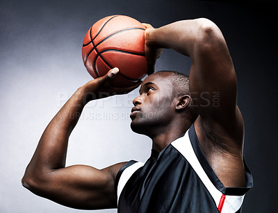 Buy stock photo A healthy young male basketball player in free throw pose against a grunge background