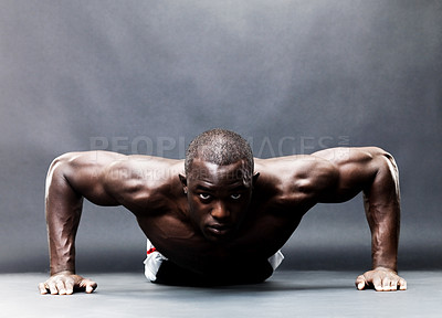 Buy stock photo Portrait of a muscular young man doing push ups exercise against grunge background