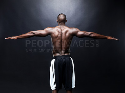 Buy stock photo Rear view of an afroamerican young man stretching his muscular arms against grunge background