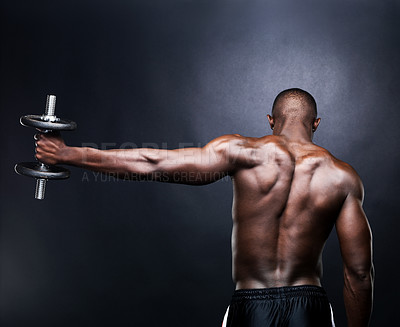 Buy stock photo Rear view of a young male bodybuilder doing heavy weight exercise  with dumbbells against dark background