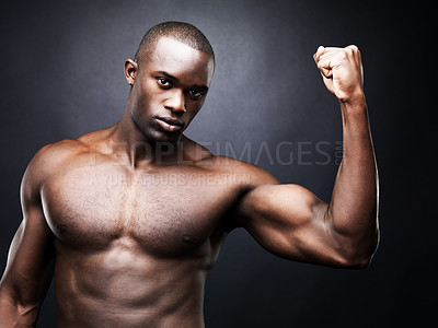 Buy stock photo Portrait of sexy masculine model showing his muscular biceps against dark background