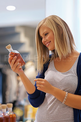 Buy stock photo Portrait of blond woman looking at the label of oil in the store
