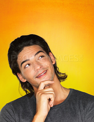 Buy stock photo Man with hand on chin looking up against yellow background