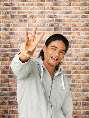 Buy stock photo Attractive man against brick wall holding up three fingers