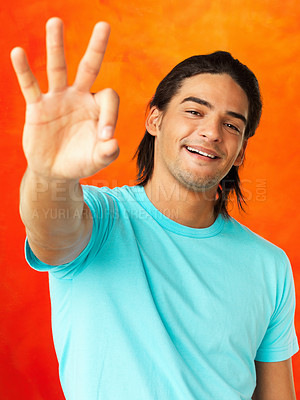 Buy stock photo Attractive young man giving ok sign on orange background