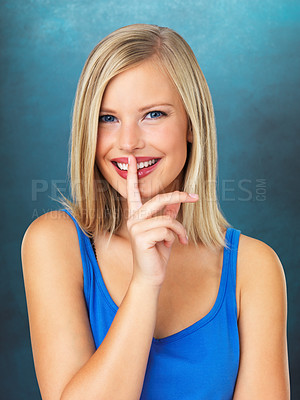 Buy stock photo Beautiful woman giving silence gesture against blue background