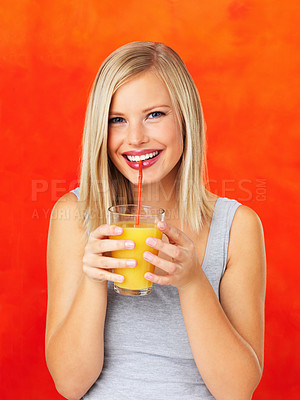 Buy stock photo Pretty woman sipping orange juice and smiling