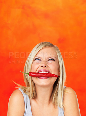 Buy stock photo Pretty woman holding red chilly with teeth and looking up at copyspace