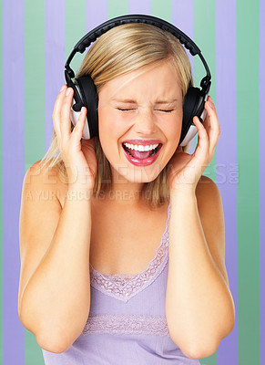 Buy stock photo Portrait of excited young woman listening to music on headphones