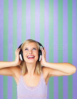 Buy stock photo Beautiful woman looking up with headphones on