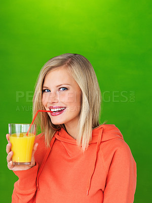 Buy stock photo Pretty woman sipping juice on green background