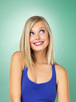 Buy stock photo Smiling young woman glancing upward on green background