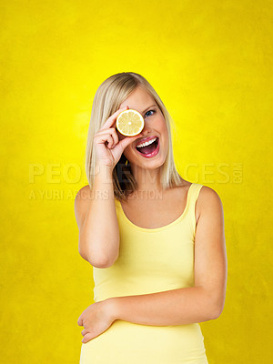 Buy stock photo Woman holding up lemon up to her eye against yellow background