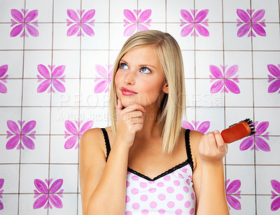 Buy stock photo Pretty blonde woman deep in thought while holding brush