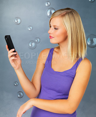 Buy stock photo Pretty woman looking serious while looking at her cell phone
