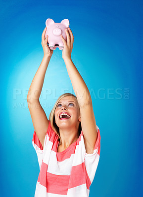 Buy stock photo Blonde woman holding piggybank over her head