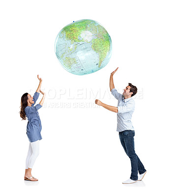 Buy stock photo Portrait of a happy young couple playing with a globe over white background