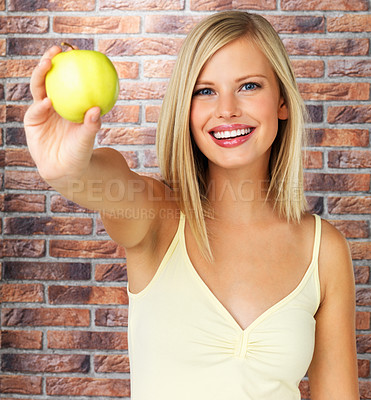 Buy stock photo Pretty woman against brick background, holding out apple for you