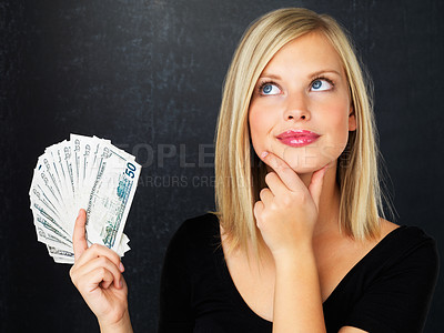 Buy stock photo Pretty woman holding fan made of money and contemplating