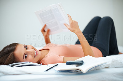Buy stock photo Happy girl lying on bed and holding up book