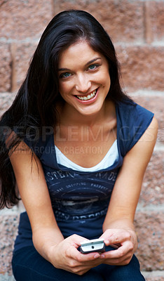 Buy stock photo Portrait of a relaxed young woman sitting with a mobile phone against the wall