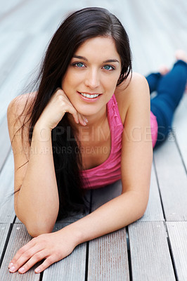 Buy stock photo Portrait of a charming young woman lying on the wooden floor