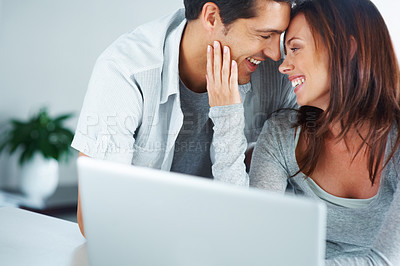 Buy stock photo Portarit of a romantic young couple at home in front of their laptop - copyspace