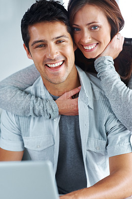 Buy stock photo Portrait of a cute young woman hugging her boyfriend from behind and smiling