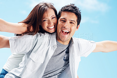 Buy stock photo Handsome young man carrying his girlfriend on his back with their hands outstretched - Outdoor