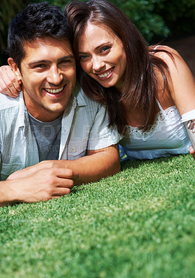 Buy stock photo Portrait of a happy young couple smiling together while lying on bright grass outdoors - copyspace