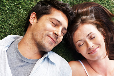 Buy stock photo Closeup portrait of a lovely young couple lying on grass - Outdoor