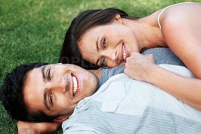 Buy stock photo Portrait of a beautiful young couple smiling together while lying on grass - Outdoor