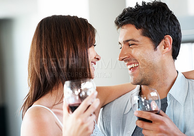 Buy stock photo Portrait of a happy young couple holding glasses of red wine and celebrating