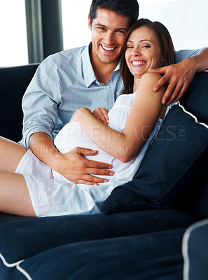 Buy stock photo Young pregnant woman and her husband smiling together while sitting on the sofa