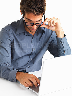 Buy stock photo Young executive adjusting glasses while working on laptop