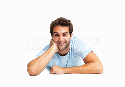 Buy stock photo Man resting hand in face while lying on his stomach