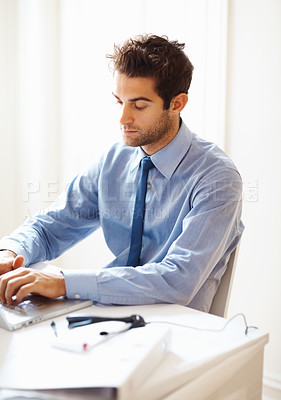 Buy stock photo Portrait of young executive busy working on laptop