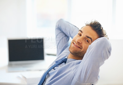 Buy stock photo View of executive leaning back in chair with laptop in background