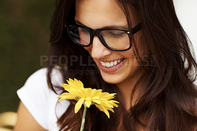 Buy stock photo Portrait of a happy young woman in glasses looking at a yellow flower