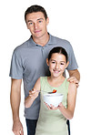 Small girl eating fruit salad while standing with her father