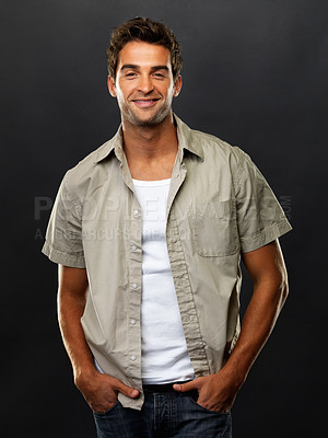 Buy stock photo Portrait of smart young man standing with hands in pockets on black background and smiling