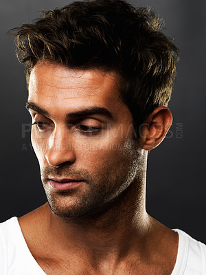 Buy stock photo Closeup of a handsome young man looking away on black background while feeling down
